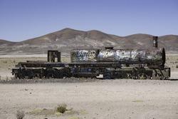 Old rusty locomotive with open steam boiler.Uyuni, train cemetery, Bolivia. Blue sky background
