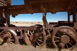 Old rusty locomotive with wheels in the close up .Uyuni, train cemetery, Bolivia. Blue sky background