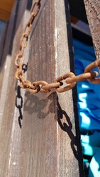 Old rusty metal chain links closeup on rough wooden background in bright sunlight with dark shadows. Broken iron chains as freedom slavery symbol