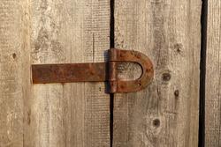 Old rusty metal door hinge. Door hinge on a wooden wall.