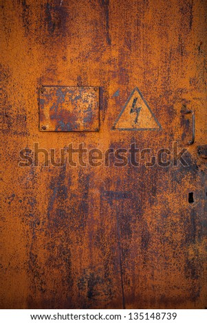 "Old rusty metal door with the sign ""Danger High Voltage"""