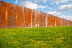 Old rusty metal fence wall on green meadow with blue sky in back