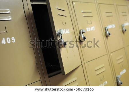 Old, rusty, metal lockers with locks. Represents concepts such as safety, security, theft, or general themes such as sports. - stock photo