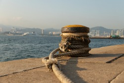 Old rusty metal pier or dock post, boat or ship tying berth, with ropes at cargo pier at Water front at Western District Public Cargo Working Area, Kennedy town, Victoria Harbour, Hong Kong