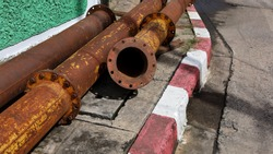 Old rusty metal pipes on the pavement. Drain piles are made of old and rusted steel with joints on the pavement, beside green walls and concrete roads. With a copy area. selective focus