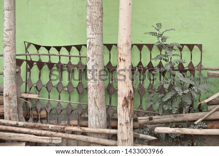 Old rusty metallic bed bases behind tree trunks and wood stakes left aside leaning against the green outer wall of a house in the Livestock Market area. Hotan-Xinjiang Uyghur Autonomous region-China. #1433003966