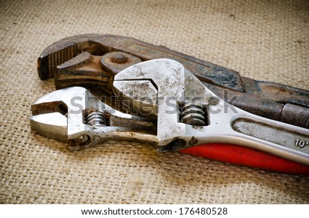 Old rusty monkey wrench and adjustable wrench on brown sack