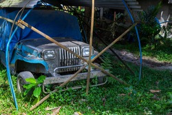 Old rusty offroad car in handmade garage, philippine lifestyle photo. Vintage jeep car in tropical garden of South Asia. American car industry in asian life. Rustic transport in the Philippines