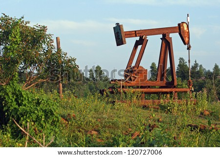 Old, rusty oil pump in a field near a forest in central Oklahoma