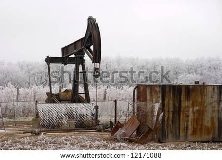 Old rusty oil well on a winter landscape