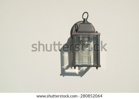Old rusty outdoor lamp attached on the white wall with its shadow.