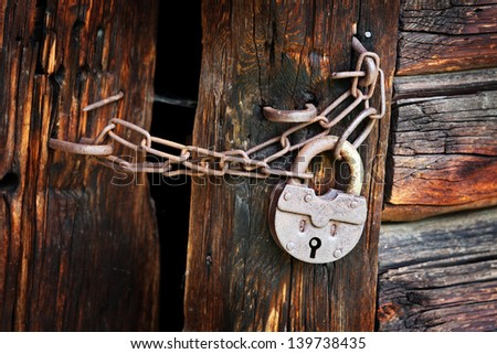 Old rusty padlock and chain on the rural wooden gate