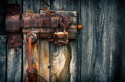Old rusty padlock on wooden door