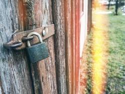 Old rusty padlock on wooden door. Abstract.