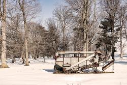 Old Rusty Piece of Farm Equipment in a Snowy Winter Landscape Sepia Tone