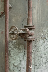 Old rusty pipe with valve, close-up.
