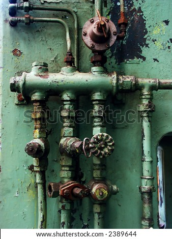Old rusty pipes and valves with water leaks