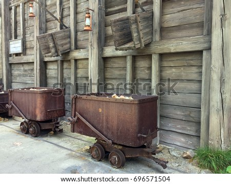 Old rusty rail cars being loaded with rocks