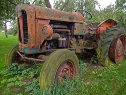 Old rusty red vintage tractor in a farm