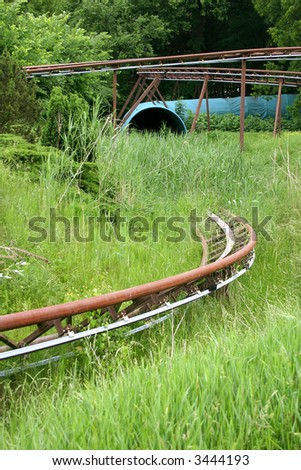 old rusty rollercoaster overgrown by grass and bushes