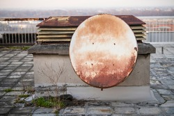 Old rusty satelite antenna dish on roof of the building hangs on the rooftop chimney ventilation system. Parabola satellite receiver. Outdated corroded equipment.
