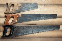 old rusty saws on the wooden background