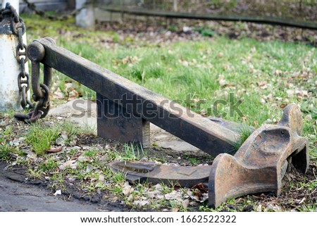 Old rusty ship anchor lies on the ground. Stockfoto ©