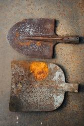 Old rusty shovel and bayonet spade on a rusty sheet of iron. Scrap metal. Close-up.