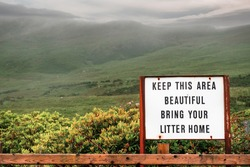 Old rusty sign with message keep this area beautiful, bring your litter home. Green mountains in the background covered with low clouds. Connemara, Ireland.