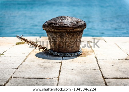 Old rusty steel mooring bollard pole on a pier. The best way for boat or ship mooring in harbor. Croatia, Silba.