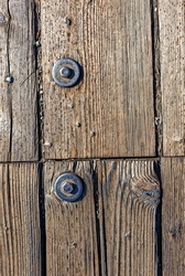 Old rusty timber bolt inside a wooden floor of what used to be a pier