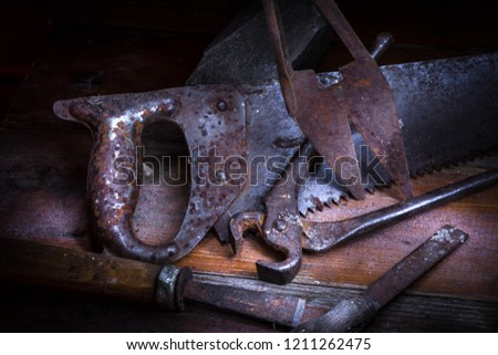Old rusty tool in the dark room, totally dark place, playing with lights, old stuff, nippers,  hacksaw,  scissors, chisel on wooden table.