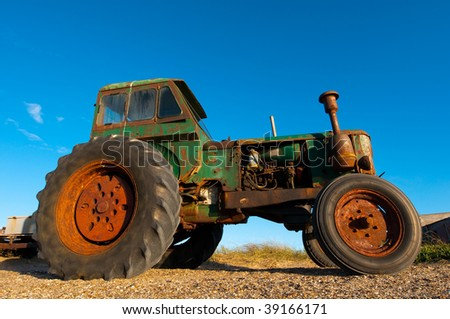 Old Rusty Tractor still working, shot with a wide angle lens - stock photo