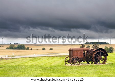 Old rusty tractor with storm weather in the background