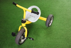 old rusty tricycle bike on artificial turf.