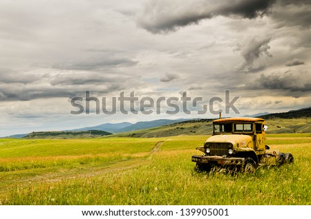 Old Rusty Truck in Middle of Field and Stormy Clouds