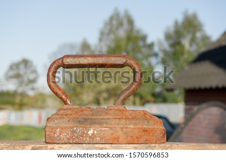 Old rusty Vintage iron with big corroded handle for ironing. Antique household item on sunny day. #1570596853