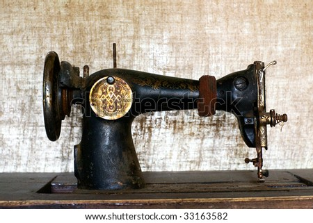 Old rusty vintage sewing machine against blurred linen