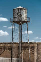 Old rusty water tower next to a brick wall with platform blue sky - concept supply business industry old vintage utility infrastructure storage reservoir industry metal construction scarce resource