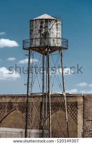 Old rusty water tower next to a brick wall with platform blue sky - concept supply business industry old vintage utility infrastructure storage reservoir industry metal construction scarce resource #520149307