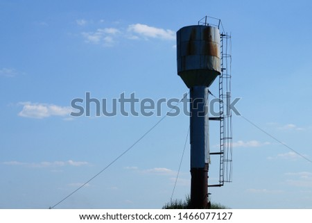 Old rusty water tower on sky background #1466077127