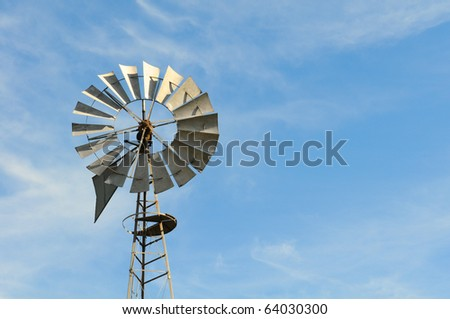 Old rusty windmill weather vane against a blue sky with white wispy clouds. Horizontal format with copy space on the right side.
