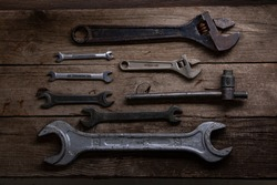 old rusty wrenches on a wood table, top view