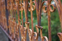 old rusty wrought iron railing,coating was peeling off. background blurred green nature (selective focus).concept for rust cleaning abrasive, products, service ect.