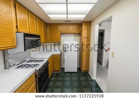 Old 1980s condo kitchen with oak cabinets, tile countertops, gas stove and green flooring.