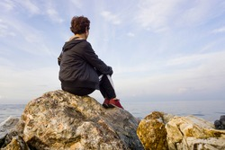 Old sad depressed woman sit alone on rocks, looking at distant sea / seascape horizon. Time to go, say goodbye. Miss someone. Desire, hope to go far away. Unhappy woman feel lonely at seaside outdoor