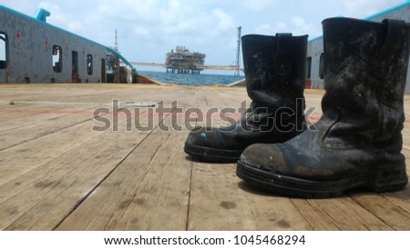 Old safety shoes, one of the PPE accessories used for personal safety. Put on wooden floor of ship deck, with sky and oil platform. As a background, At offshore working area #1045468294