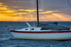 Old sailboat anchored in choppy water as the sun begins to rise.