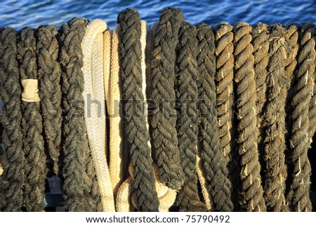 Old sailing ropes on the blue sea background