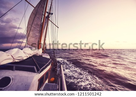 Old sailing ship at sunset, travel and adventure concept, color toned picture.